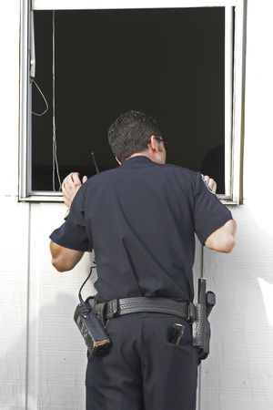narc: Police investigating a break-in at a local company, window pride open Stock Photo