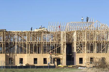 New building under construction, carpenters installing frame work photo