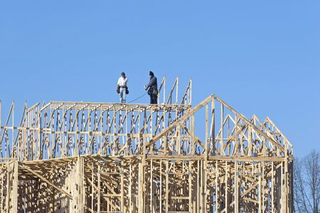 New building under construction, carpenters installing frame work Stock Photo