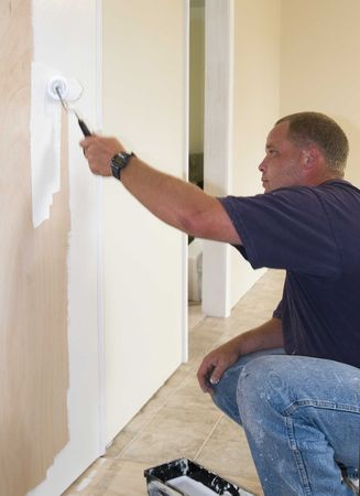 Painter painting interior of house that is on the market to be sold,