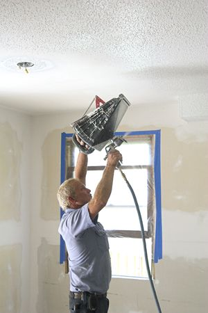refinish: Painter painting interior of house that is on the market to be sold,