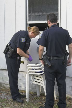 dusting: Police woman dusting for finger prints at crime scene