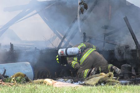 burned out: Fire fighters look for victums in debree of burned out home
