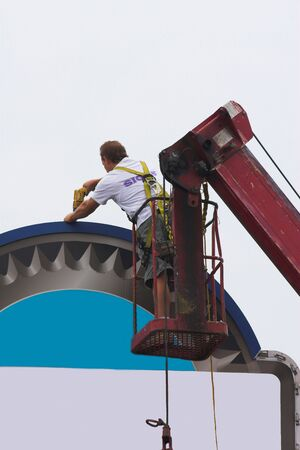 local business: Man installing new commercial sign for local business