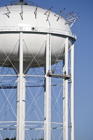 scaffolds: Painters painting gaint water tower to complete the construction of this new city water reservoir