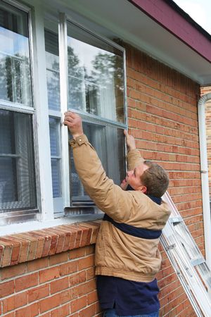 Carpenter installing new storm windows, home is being updated to be sold