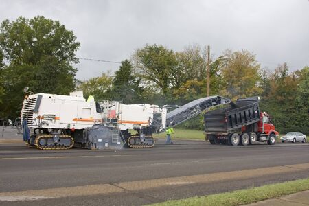 dumptruck: very large pavement removing machine is tearing old asphalt off the road and loading it to a dumptruck, asphalt will be recycled again to re-black top road Stock Photo