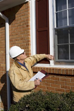 Home inspecteur op zoek naar mogelijke problemen voor een potentiële koper, zoekt nodig reparaties