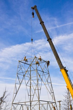 light transmission: Contractors are installing new high voltage transmission towers to carry electricity across the country, parts are lifted with a large crane