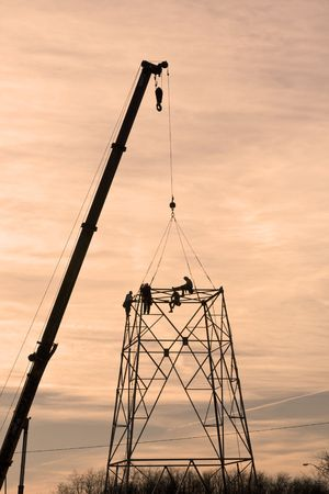 climbing cable: Contractors are installing new high voltage transmission towers to carry electricity across the country, parts are lifted with a large crane
