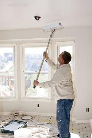 updating: Contract painter updating colors of walls and painting ceilings bright white to speed up selling of home