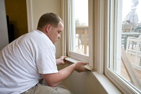 Carpenter repairing window frames, home is being updated to be sold