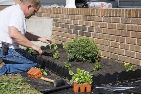 paysagiste: Équipez planter des fleurs dans le jardin, shabillant vers le haut du paysage pour aider à se vendre à la maison
