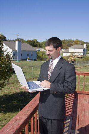 homeoffice: Young executive working at home through the internet ,standing on deck and communicating with his office computer