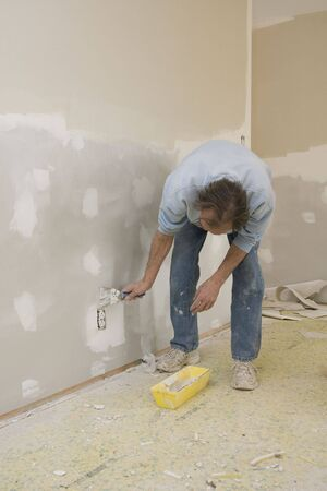 home repairs: Worker doing spot repairs on house walls, getting ready for new coat of paint, will put home on realstate market to sell
