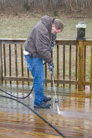 maintain: Worker pressure washing deck on rear of house
