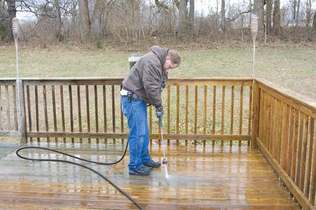 house worker: Worker pressure washing deck on rear of house