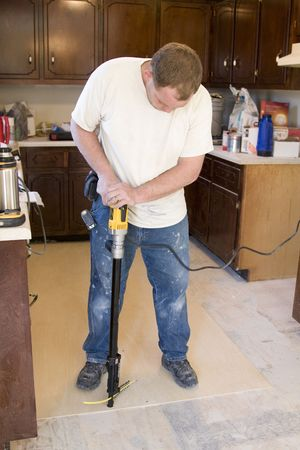 Contractor installing sub base for new flooring, will be installing vinyl and tile to update kitchen and dining room, will put home on real-state market to sell  Stock Photo