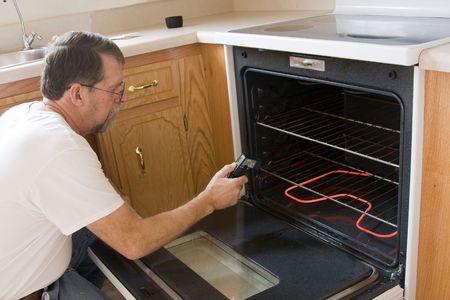 estufa: Reparaci�n hombre pruebas el funcionamiento de la estufa y horno Foto de archivo