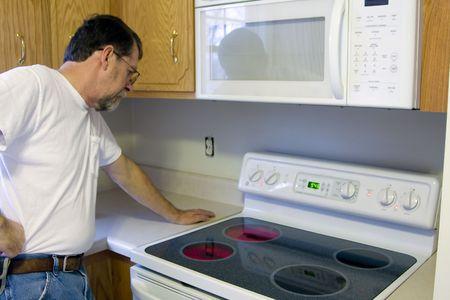 estufa: Reparaci�n hombre pruebas el funcionamiento de la estufa y horno