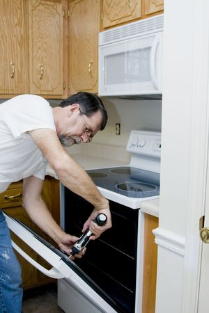 Repair man testing the operation of stove & oven found over door mis aligned Stock Photo
