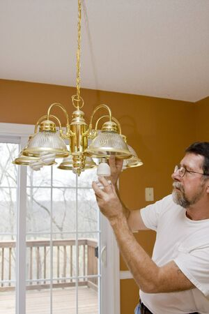 Home owner install energy saving light bulbs in dining room,bathrooms & kitchen to save energy & money Stock Photo - 2506003