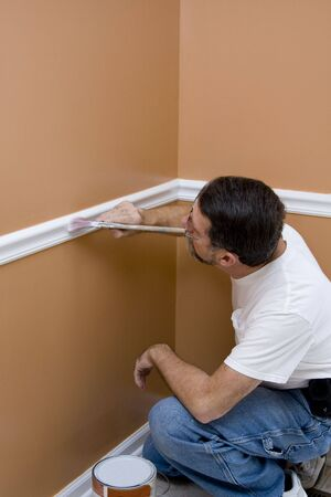 Contract painter updating colors of walls and painting ceilings bright white to speed up selling of home