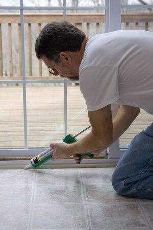 caulk: Contractor caulking around glass door frame, sealing from possible air leaks, conserving energy Stock Photo