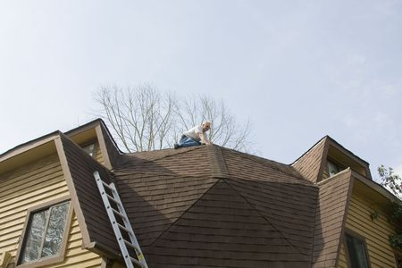 Roof inpector check for damage after recent wind storms, many roofs were damaged Stock Photo