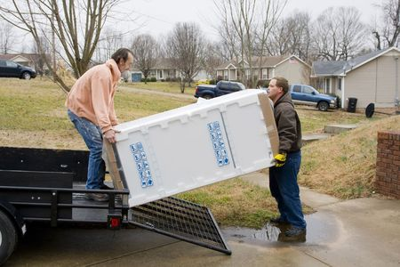 frig: Two men delivering a new frig to local resident,  home owners paid for store delivery to their home Stock Photo