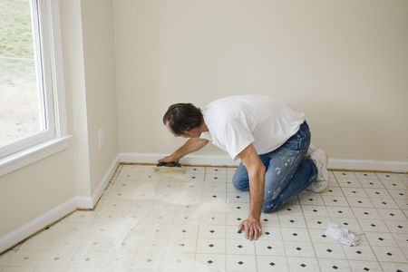 Contractor installing glue base for new flooring, will be installing vinyl & tile to update kitchen & dining room, will put home on real-state market to sell