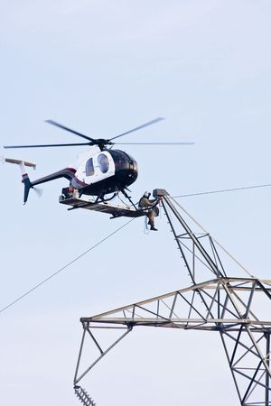 on the skids: Contractors are installing new high voltage transmission towers to carry electricity across the country, final work is done with worker sitting on bench below helicopter on the skids making final connections to high voltage lines