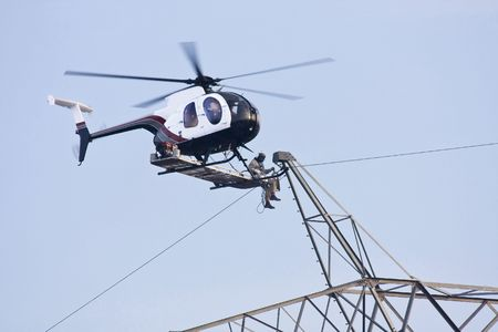 Contractors are installing new high voltage transmission towers to carry electricity across the country, final work is done with worker sitting on bench below helicopter on the skids making final connections to high voltage lines