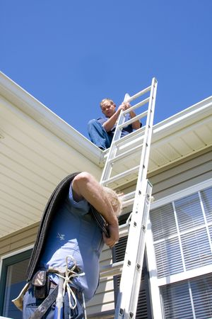 Roofing contractor repairing damaged roof on home