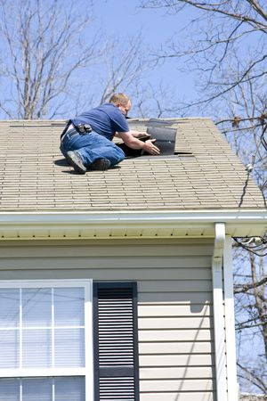 property ladder: Roofing contractor repairing damaged roof on home after recent wind storms, many roofs were damaged
