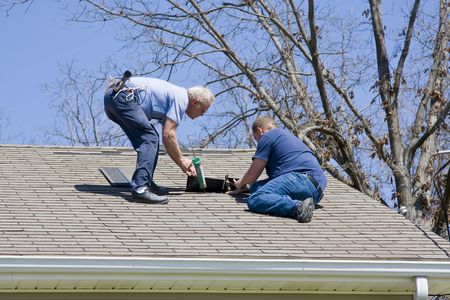 Roofing contractor repairing damaged roof on home after recent wind storms, many roofs were damaged Stock Photo - 2743649