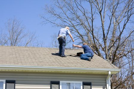 Roofing contractor repairing damaged roof on home after recent wind storms, many roofs were damaged Stock Photo - 2739721