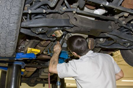 Mechanic removing transmission from pickup truck, transmission needs to be replaced,work will be done under warranty