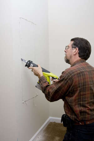 sheetrock: Electrician cutting sheetrock to get access to wiring inside wall under stairway