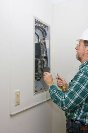 Inspector hired by future home owner, checking circuit breakers for loose connections,defective breakers or any signs of over heating of wiring, Stockfoto