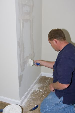 Man applying first coat of drywall compound on a large patch that was cut out to gain access to house electrical wiring for repairs & modification