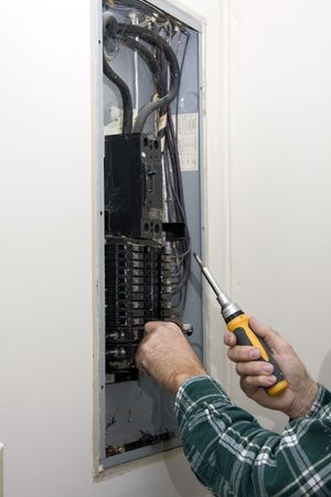 defective: Inspector hired by future home owner, checking circuit breakers for loose connections,defective breakers or any signs of over heating of wiring, Stock Photo