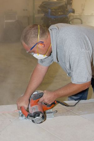 Carpenter cutting ceramic tile to prepare flloor base for new wall photo