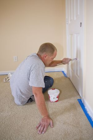 Contract painter updating colors of walls and painting doors,ceilings bright white to speed up selling of home photo