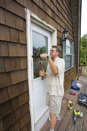 Elderly carpenter replacing exterior door frames, weather has promoted  rot & chipping of the paint
