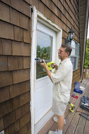 Elderly carpenter replacing exterior door frames, weather has promoted  rot & chipping of the paint Stock Photo - 3488370