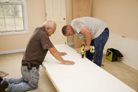 Carpenters using old door for pattern to cut out new interior doors,home will be sold on market photo