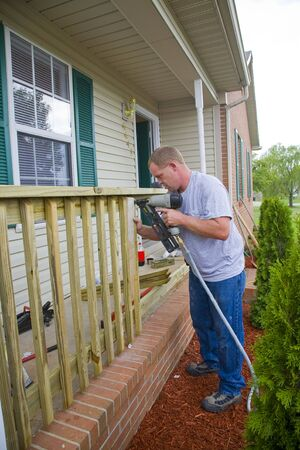 value add: Carpenter is adding rails to porch on front of house, will add value for resale Stock Photo