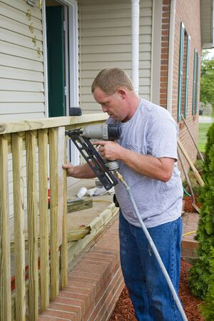 Carpenter is adding rails to porch on front of house, will add value for resale Stock Photo