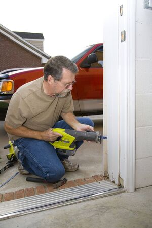 Carpenter repairing exterior door casing, weather & insects have contributed to rot at the bottom of casing Stock Photo - 3593892